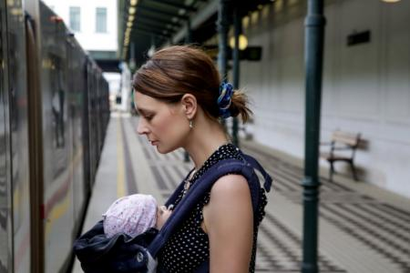 Woman getting on train with baby